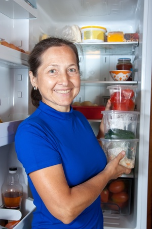 Mature woman putting   vegetables in containers   into refrigerator  at home photo