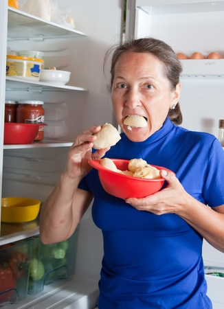 fridge: Mature woman eating potatoes near the fridge at home Stock Photo