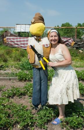 bugaboo: Donne mature fioristi vicino spaventapasseri in giardino