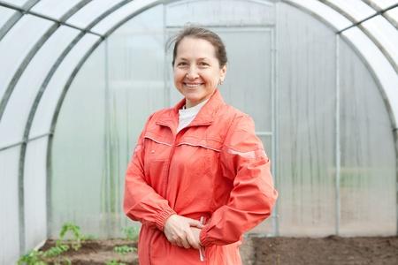 Pretty woman gardener in spring  hothouse  photo