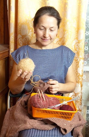 Portrait of a senior woman knitting in her room Stock Photo - 13213101