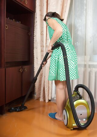 beautiful  mature housewife with vacuum cleaner in a room photo