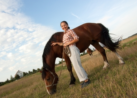 A beautiful mature woman stands next to horse with a happy smile on her face photo