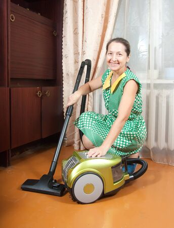 Smiling woman use vacuum cleaner in a living room photo