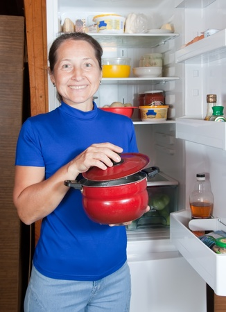 Mature woman at home with pan the fridge photo