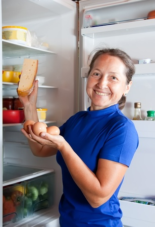 Beauty mature woman taking in fridge of   kitchen interior photo