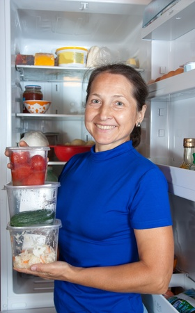 Happy woman with containers of vegetables near the fridge at home Stock Photo