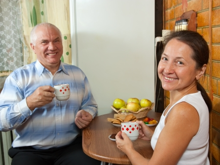 Mature couple at breakfast time at kitchen interior photo