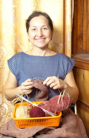 Portrait of happy and active   woman knitting with wool and metal knitting needle photo