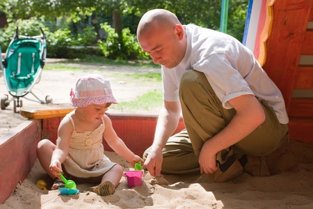 sandpit: happy dad with  toddler  playing with sand in sandbox Stock Photo