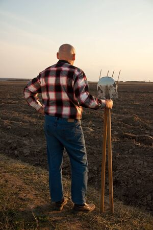 pitchfork:   male farmer with spade and pitchfork in field