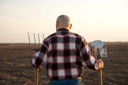 male farmer holding   shovel and  pitchfork looking at sky Stock Photo - 14335169