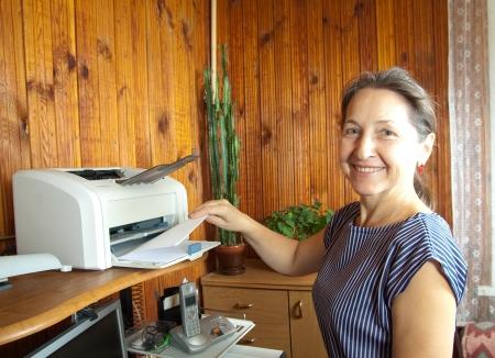 impresora: mujer de mediana edad de pie cerca de la impresora con papel Foto de archivo