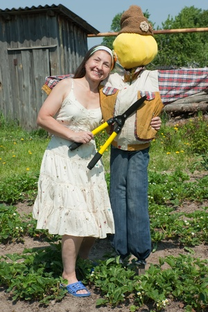 bugaboo: Female gardener in with garden tools and scarecrow at yard