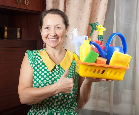 stereotypical: Mature woman holding cleaning supplies