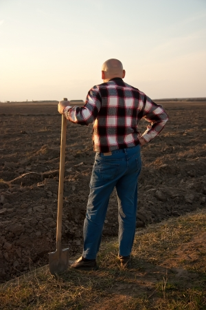 male farmer holding   shovel and looking at sky photo