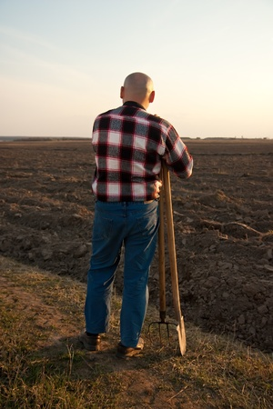 male farmer holding   shovel and pitchfork   rear view