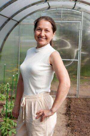 Mature gardener  standing in greenhouse  photo