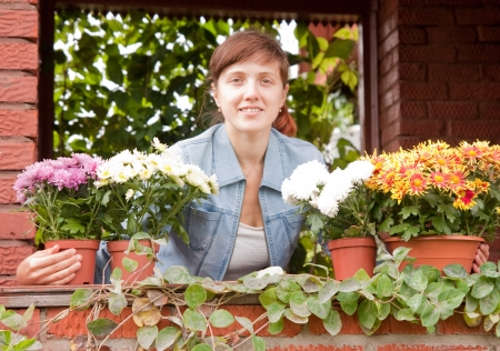 pretty girl on the porch of a country house with flowers photo