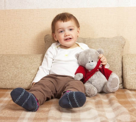 Year-old child sitting on the couch with a toy bear photo