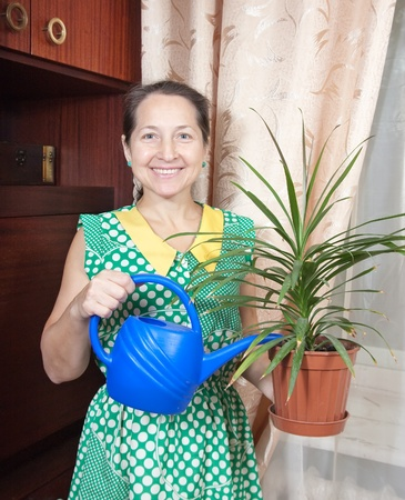 Mature woman holding flower in  pot in house photo
