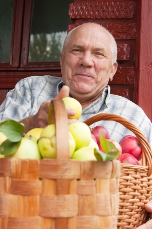 Happy elderly man with   baskets full of apples Stock Photo - 19248648