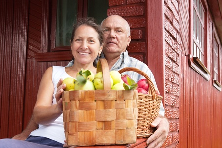 elderly couple  with  apples in summer day photo