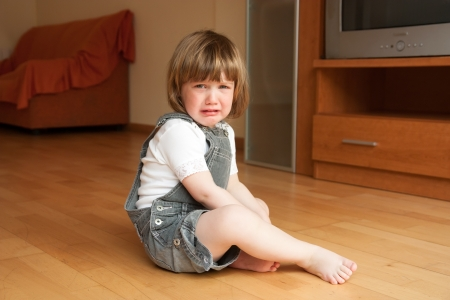 expressing negativity:  little girl sitting on the floor and crying