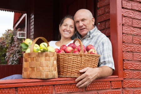 Happy elderly couple with   baskets full of apples photo