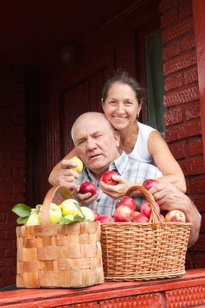 Happy seniors with apples in summer day photo