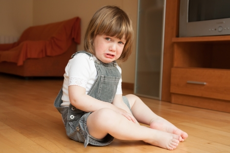 little girl sitting on the floor and crying photo