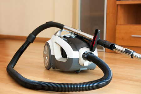 White vacuum cleaner on  parquet. close-up photo