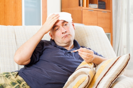 Sad  man having temperature and holding towel on his head at home