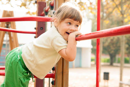 adroitness:  laughing girl in dress climbing on ropes at playground area in summer