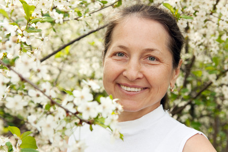 one senior woman only: Beautiful mature woman on  background of the cherry blossoms. Stock Photo
