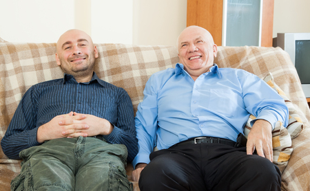 Two men siting on  couch at home photo