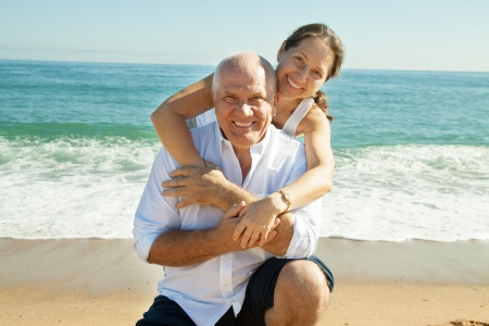 Happy senior man and mature woman together against sea in summer