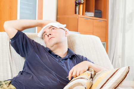 Suffering   man in plaid stupes  towel to his head