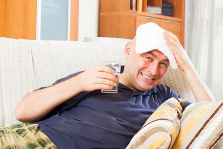 sick   man uses handkerchief on his head in home Stock Photo