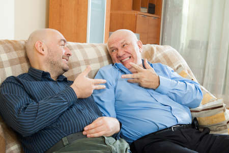 two men talking:  Two men talking on the couch at home Stock Photo