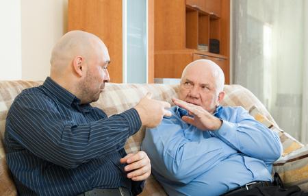 uomini maturi: Uomini maturi che comunicano sul divano di casa Archivio Fotografico