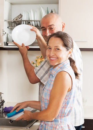 Positive housewife and her husband  washing plates with sponge  photo