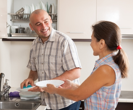 Family washing plates with sponge in domestic kitchen photo