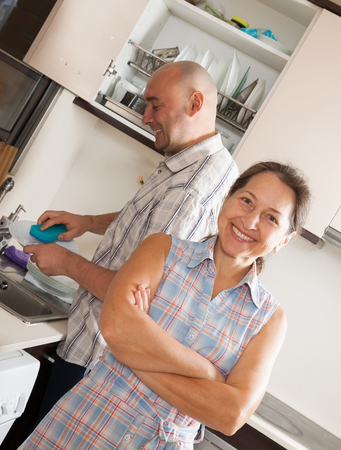 Smiling woman and man washing dishes in the kitchen photo