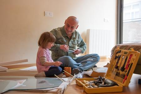 Man with child repairing furniture photo