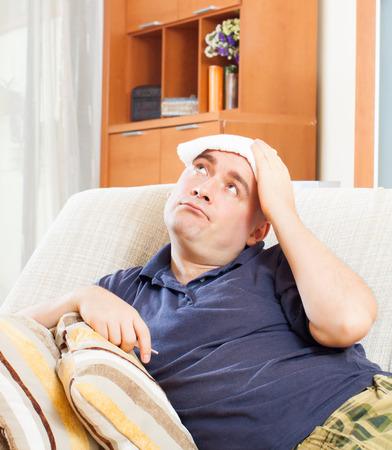 sick   man uses handkerchief on his head in ho Stock Photo