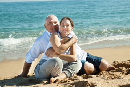 Happy senior man and mature woman together against sea in summer photo