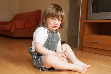niño llorando: niña sentada en el suelo y llorando
