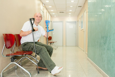 hospital corridor: man with  plaster on his leg sits in  hospital corridor Stock Photo