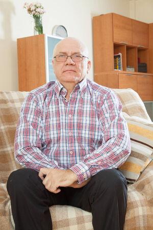 casualy: portrait of quiet grizzled senior man in interior